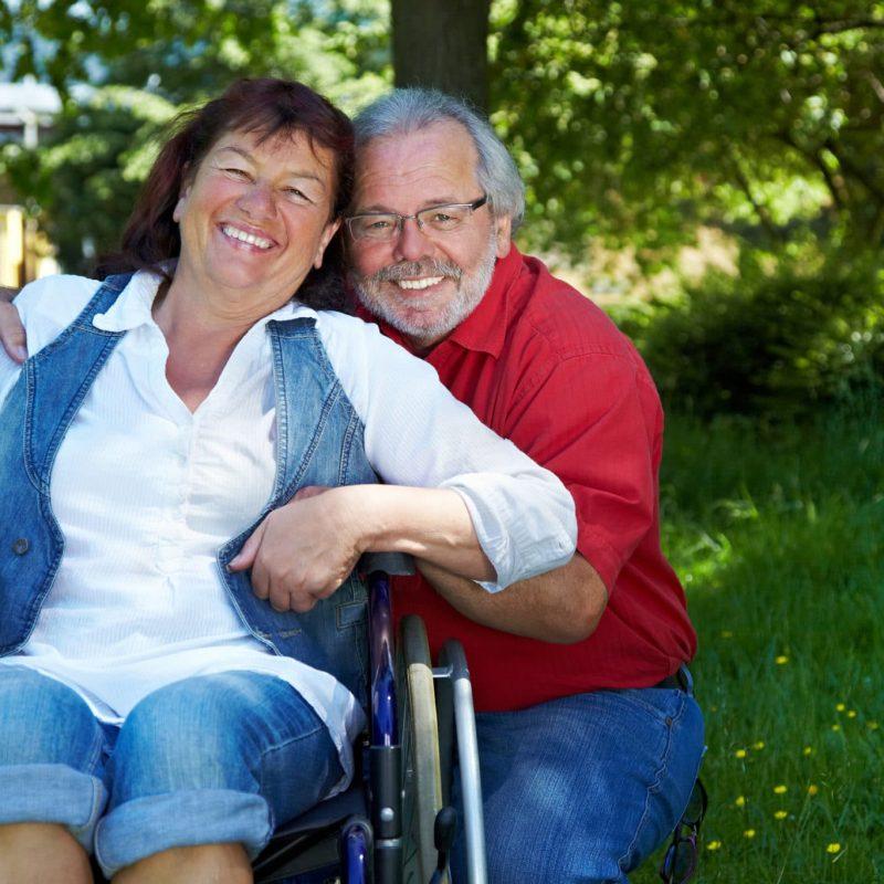 Älterer Mann mit lachender Seniorin im Rollstuhl im Park